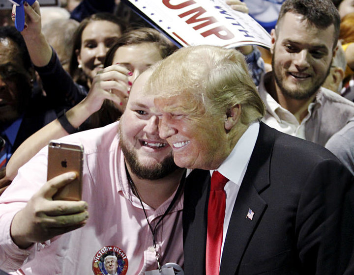Republican U.S. presidential candidate Donald Trump poses with a supporter following a campaign rally at the Georgia World Congress Center in Atlanta, Georgia February 21, 2016. REUTERS/Tami Chappell - RTX27YLZ